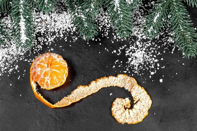 Mandarin with peeled peel on a dark background with snow