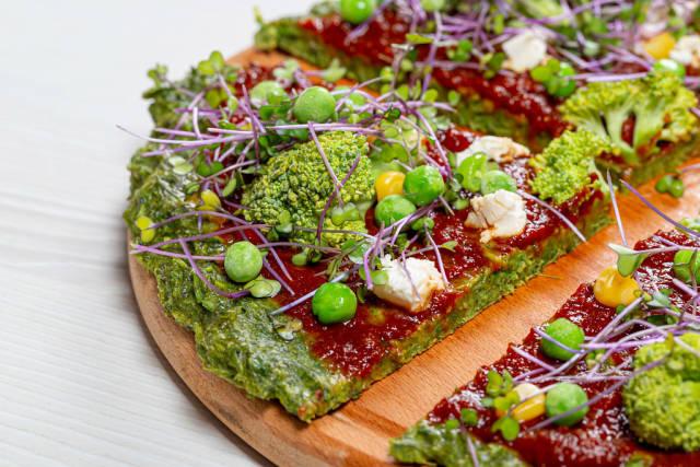 Vegetarian pizza with micro-green cabbage, tomato sauce, broccoli, corn, peas and feta cheese