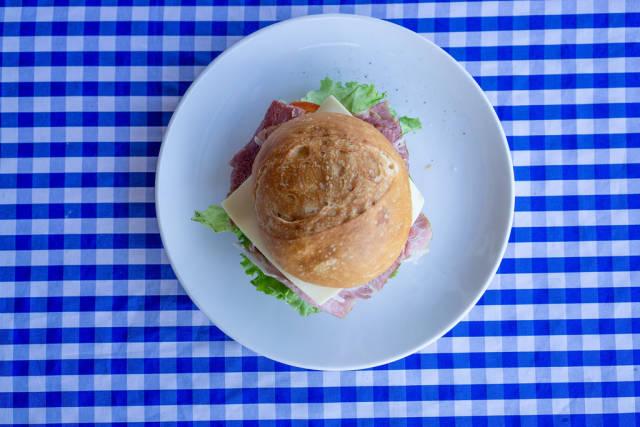 Belegtes Brötchen mit Schinken, Käse, Tomaten, Gurken, Salat und Remoulade auf einem Teller von oben fotografiert