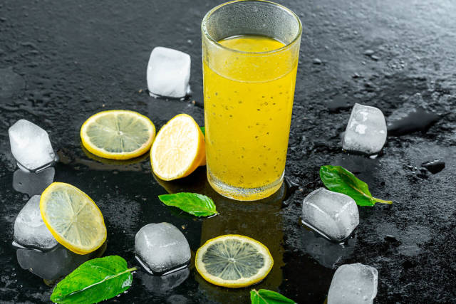 Yellow cocktail with ice cubes and lemon