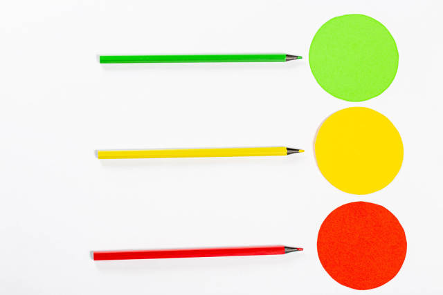 Yellow, red and green circle with colored pencils on white background