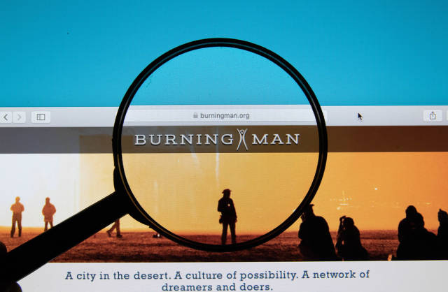Burning Man logo on a computer screen with a magnifying glass