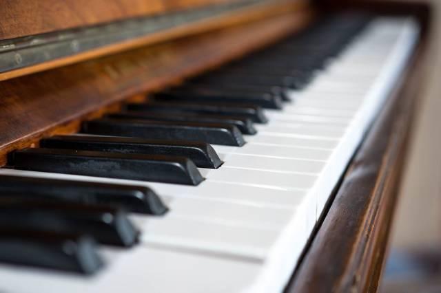 Piano keys close up diagonal view of a dark brown and wooden piano