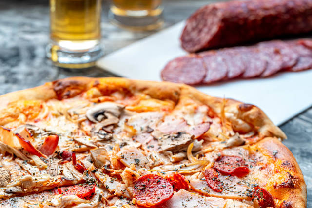 Pizza cold cuts with ham, chicken and smoked sausage on the grey table