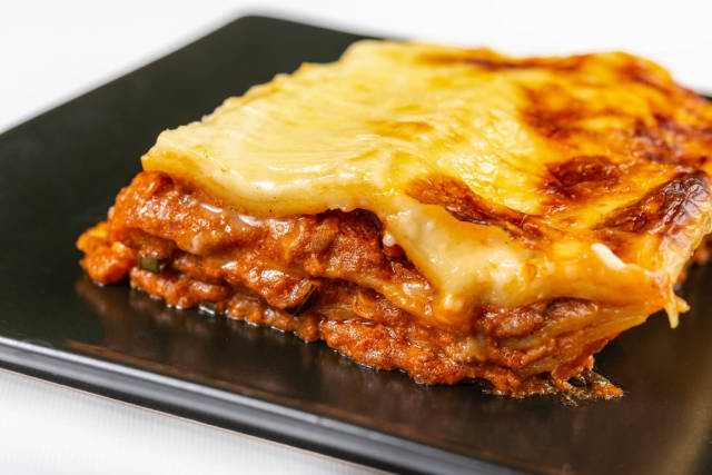 Served Lasagna on the black square plate