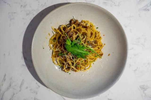 Spaghetti Bolognese mit Geriebenem Käse und Rucola auf einem Teller von oben fotografiert