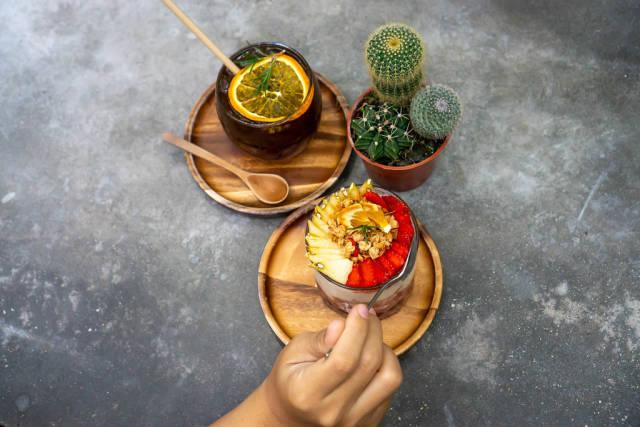 Kaktus und Cold Brew Kaffee mit Orangen neben einem Erdbeer-Apfel Joghurt und Hand mit Löffel
