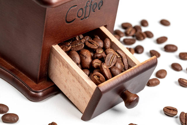 Close-up of roasted coffee beans in coffee grinder box