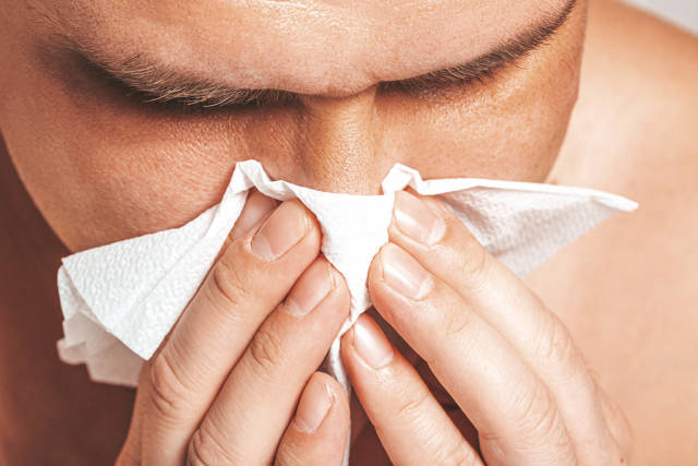 The concept of ill. The man blows his nose into a napkin