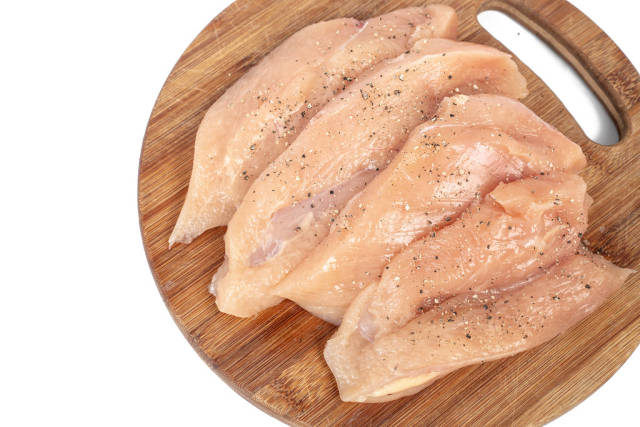 Raw Chicken Breasts with spices on the wooden board