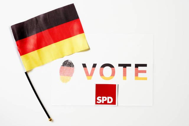 """Abstimmung für die SPD bei der Bundestagswahl 2021: Zettel mit Schrift """"Vote"""" und deutsche Flagge"""
