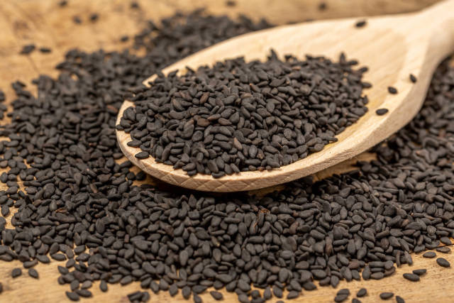 Black natural sesame seeds with wooden spoon