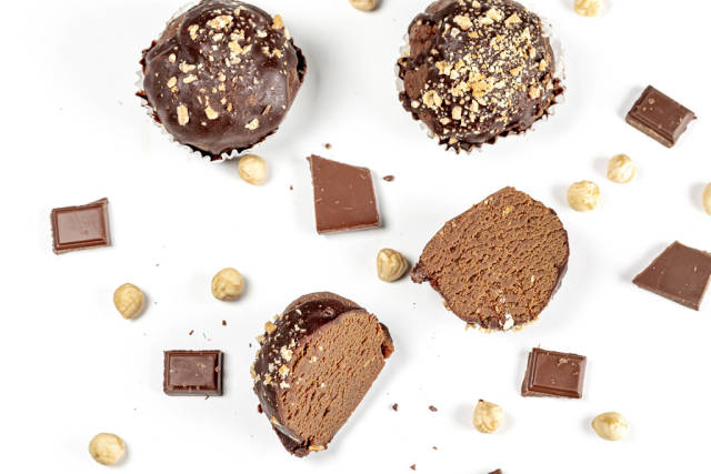Chocolate cakes with chocolate pieces and hazelnuts on a white background