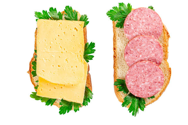 Cheese and smoked sausage sandwiches with fresh parsley leaves, top view