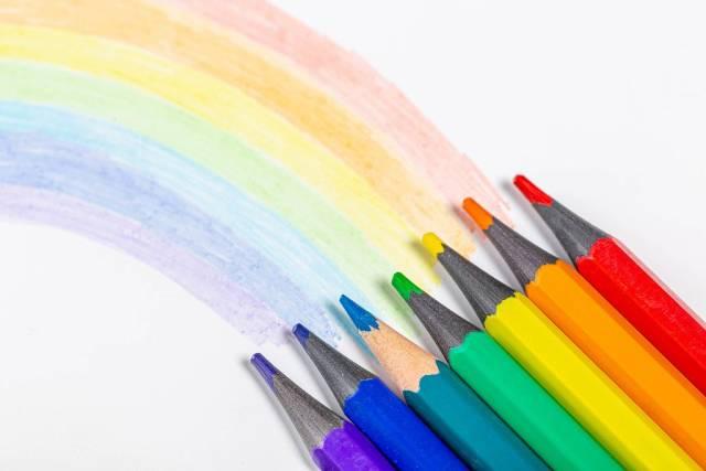 Sanfter Regenbogen auf weißem Hintergrund mit bunten Holzstiften fokussiert
