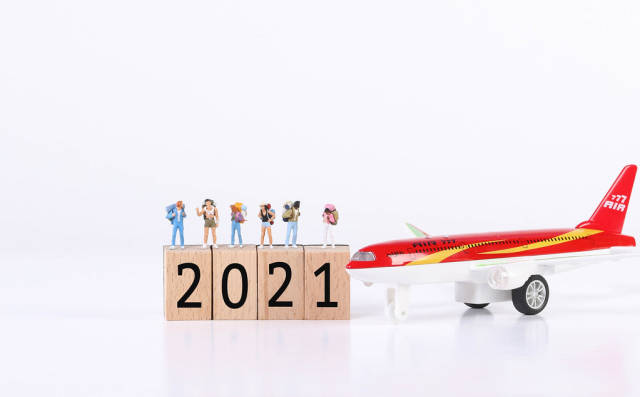 Miniature travelers with airplane and wooden blocks with 2021 text