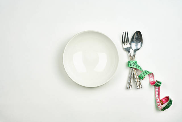 Empty white plate with a spoon and fork wrapped in measuring tape on white background. Diet concept