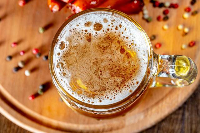 Top view a glass of beer on a wooden Board with spices (Flip 2019)