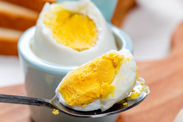 Close-up of a piece of boiled egg in a spoon. The concept of Breakfast
