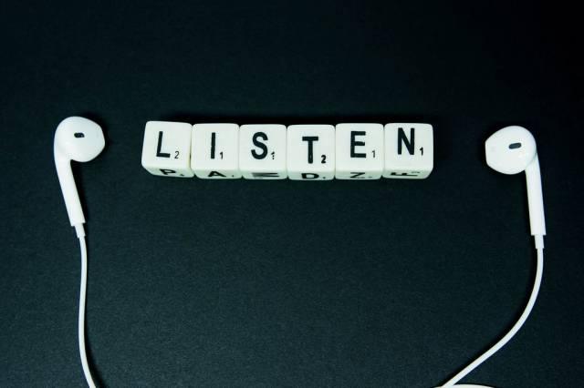 Schriftzug LISTEN aus Würfeln gebildet zwischen weißen Kopfhörern