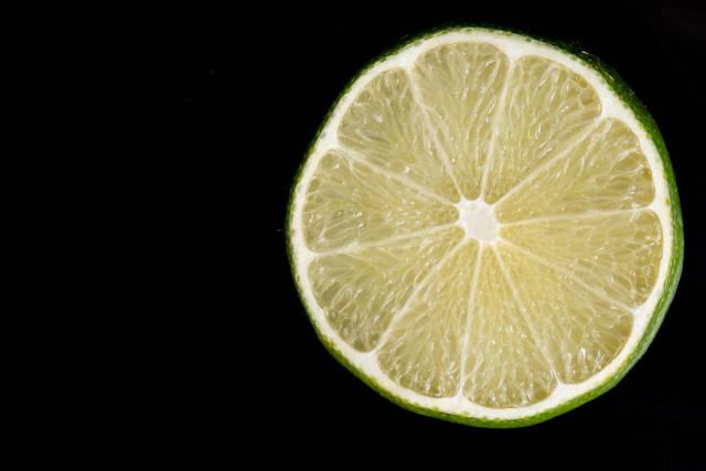 Slice of Lime fruit on the black reflective background
