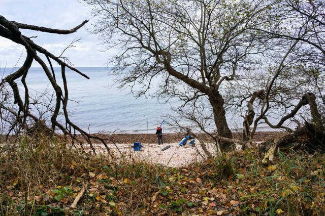 Lone fisherman on the Baltic sea coast with a fishing rod
