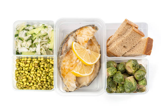 Lunch boxes with fish, vegetables, mung and black bread, top view