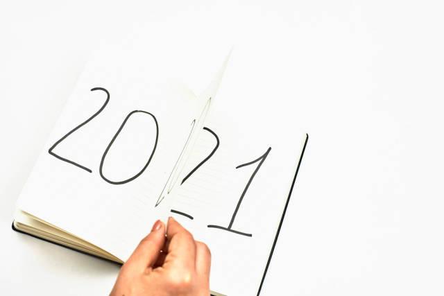 Female hand flips 2020 year. Coming new year symbol