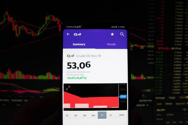 A smartphone displays the Crude Oil market value