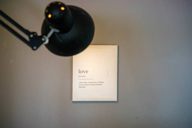 Light of a Lamp pointing at Definition of Love on a White Background as Wall Photo