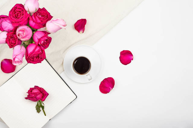 Top view of creative womans desktop with open notepad, coffee cup and rose flowers