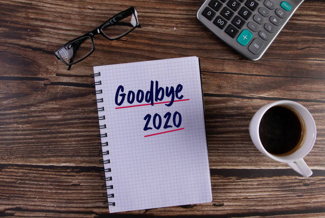 Open notebook with Goodbye 2020 text on wooden table