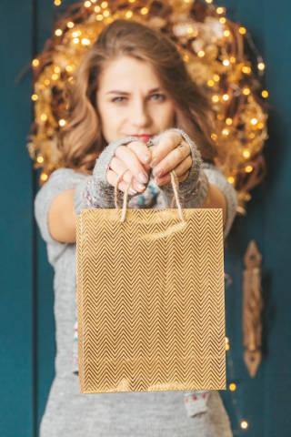 Golden gift bag in female hands, christmas gift concept