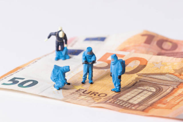 Workes in protective suits on Euro banknotes