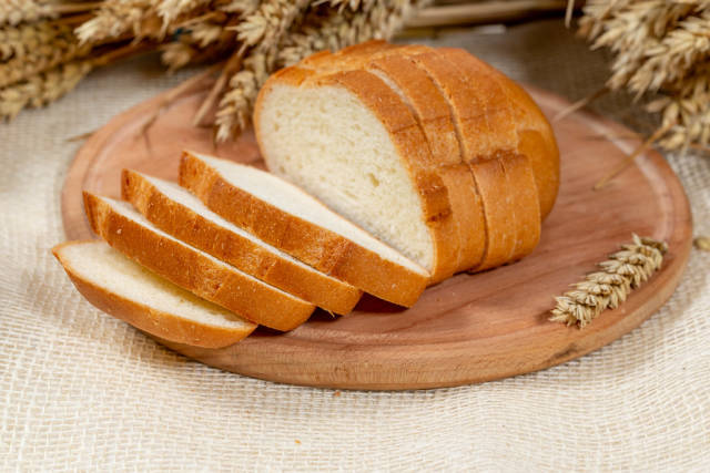 white bread sliced on a kitchen Board with wheat spikelets