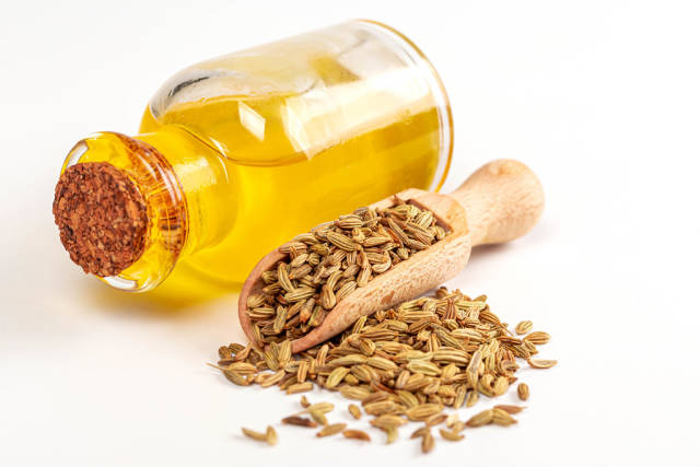 Essential oil in a bottle with fennel seeds in scoop and scattered on white background