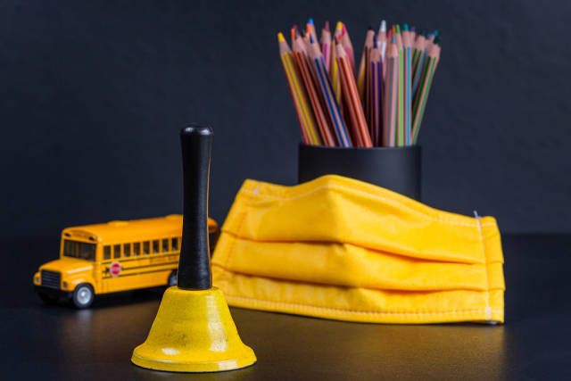 Yellow bell, mask, school bus and pencils as a symbol of the beginning of the new school year