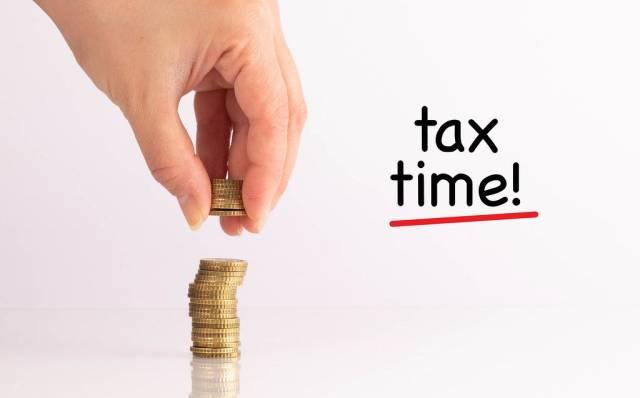 """Frauenhand hebt Münzen auf mit dem Schriftzug """"Tax Time""""  (Zeit für die Steuern)"""