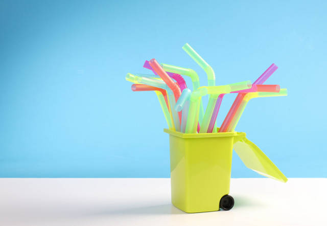 Multicoloured plastic drinking straws in the trash can