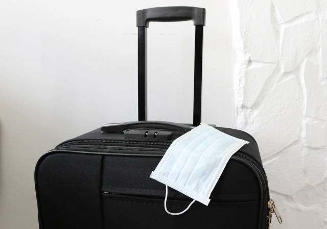 The medical mask on the suitcase as a necessary thing in travel in post covid-19 time