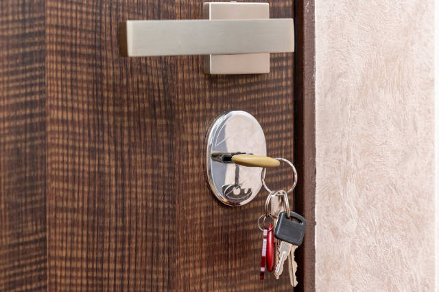 Entrance door with silver handle and keys in the keyhole