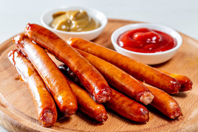 Sausages with two sauces on wooden kitchen Board