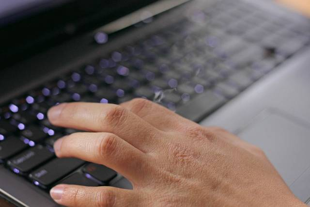 Tipping on an illuminated laptop keyboard