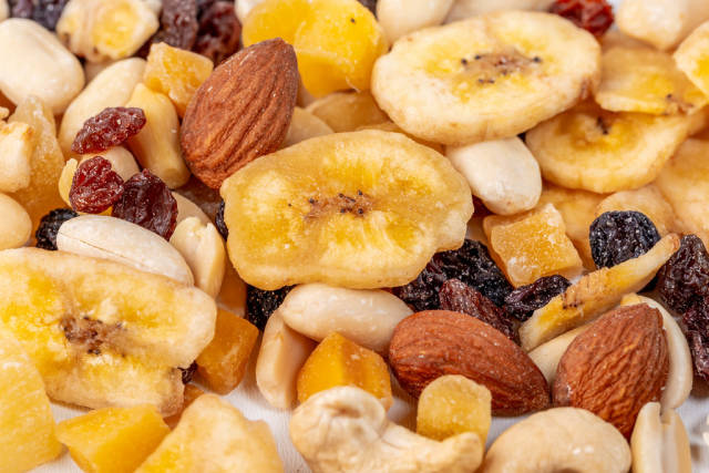 Almonds, peanuts, cashews and dry bananas, raisins with candied fruits-background