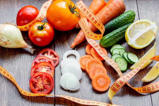 Fresh vegetables with measuring tape on the table. Healthy eating concept