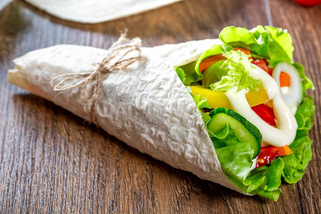 Fresh pita bread with lettuce, tomatoes, bell peppers, onions, carrots and cucumber