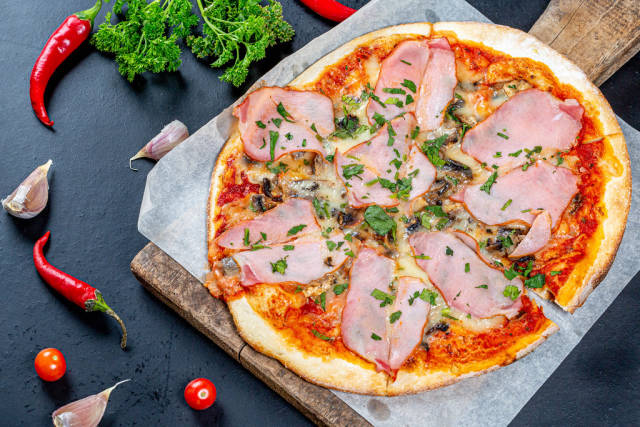 Delicious fresh pizza with ham and mushrooms