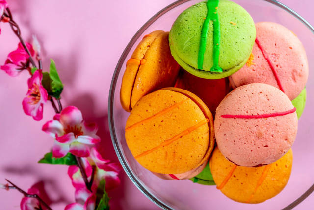 Sweet multicolored macarons on pink background.