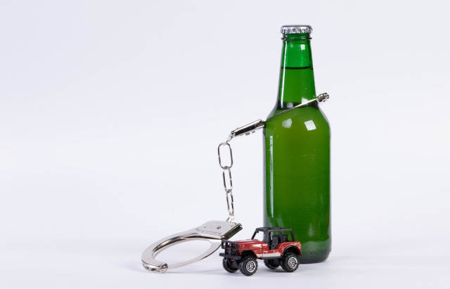 Drunk driving concept. Beer bottle chained with handcuffs with miniature car on white background