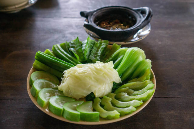 Cooked Zucchini, Cabbage, Bitter Melon, Okra and Winged Bean on a Plate with Pork Stew in a Clay Pot